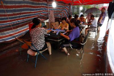 郑州市民在积水中打麻将
